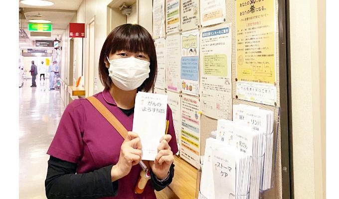 看護外来の入り口で、担当する「がんよろず相談」のパンフレットを持つ柏木さんの写真