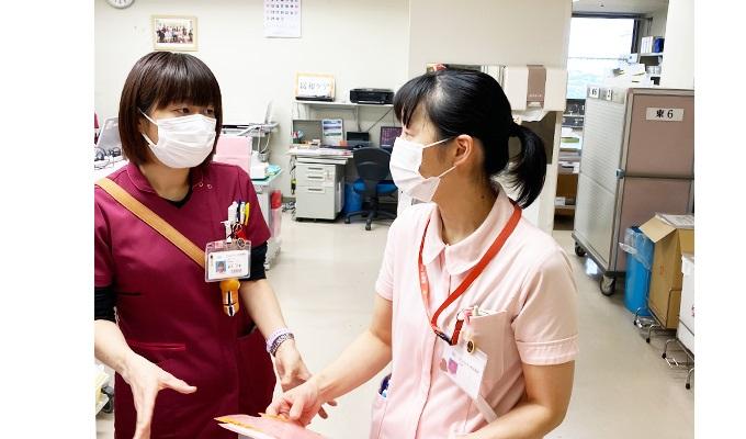 がん患者さんのケアについて病棟ナースと意見を交わす柏木さんの写真