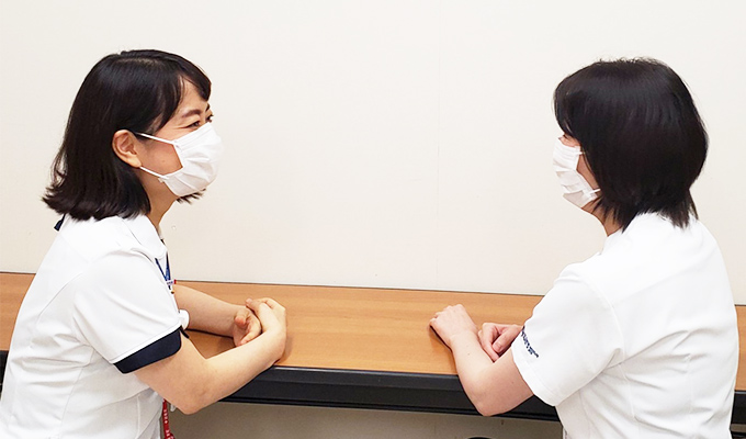 同僚ナースと笑顔で語り合う羽田さんの写真