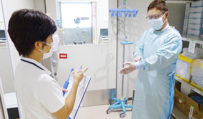新型コロナ患者対応に当たる看護師の感染対策をチェックする新改さんの写真
