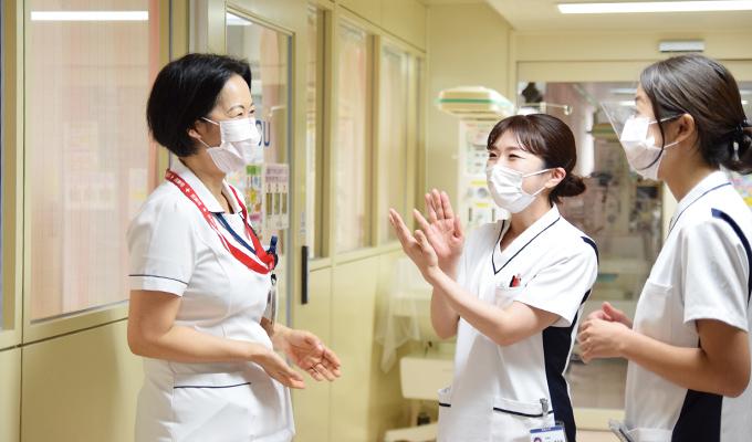 職場の周産期総合センターで同僚たちと話している井出さんの写真