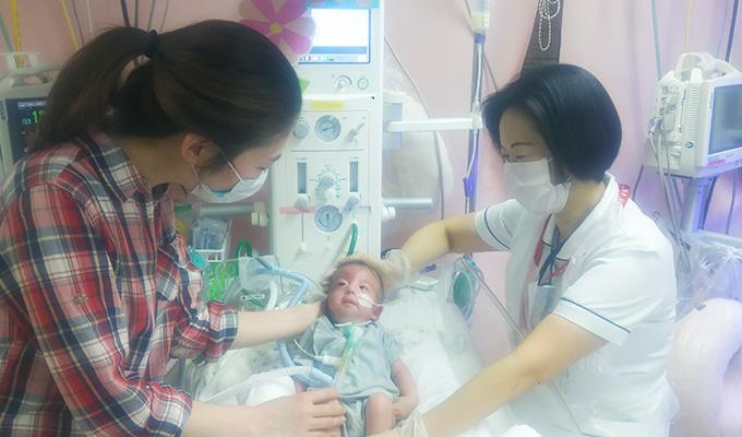 NICUでそばにいるママを見つめる赤ちゃんと、笑顔で母子を支える井出さんの写真