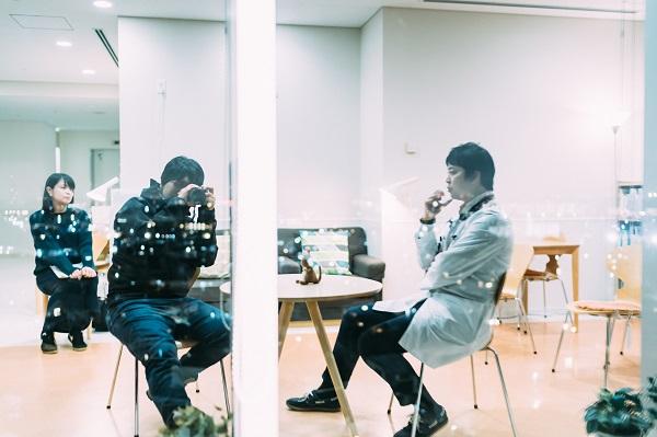 ガラス反射を利用して西先生を撮影する幡野さんの写真。
