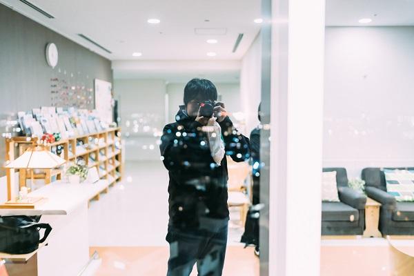 ガラス反射を利用してご自身を撮影する幡野さんの写真。