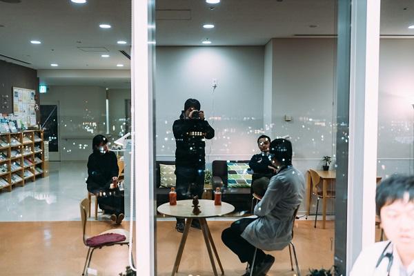 ガラス反射を利用して、対談風景を撮影する幡野さんの写真。