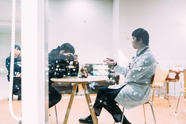 対談の風景をガラス越しに撮影する幡野さんの写真。