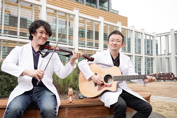 形成外科医でボーカルとバイオリン担当のToshiさん、精神科医でギターと作曲作詞担当のJyunさんの二人組音楽ユニット「Insheart(インスハート)」とかんごるーちゃんの写真。