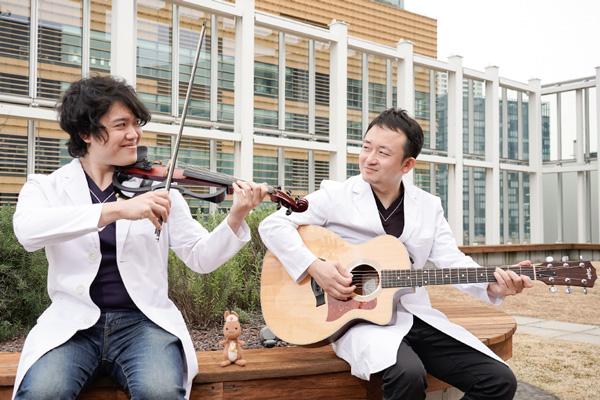 担当の楽器をかまえて目を合わせるToshiさんとJyunさんの写真