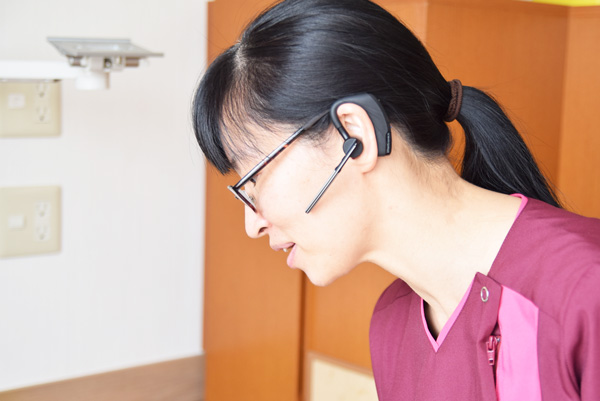 インカム型端末を耳に装着する森口さんの写真