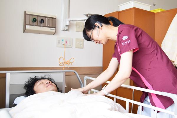 インカム型端末を着けて患者さんをケアする森口さんの写真