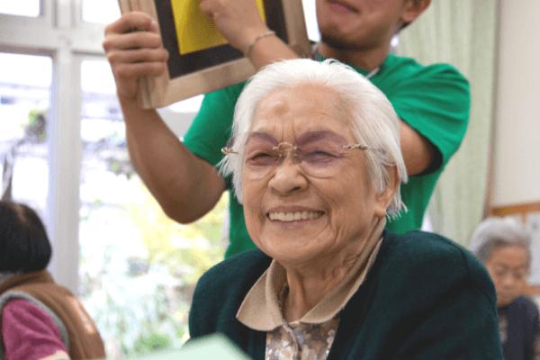 アートに触れ、笑顔の高齢女性の写真