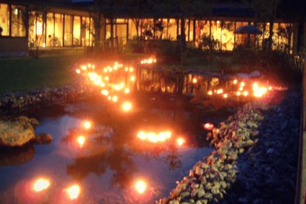 アートプログラムで高齢者とともに作ったろうそくが灯された庭の写真