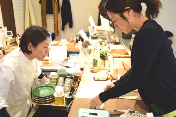 厨房の銭谷さんにオーダーを伝える佐藤さんの写真