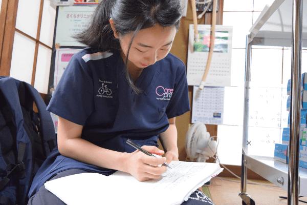 処置内容をノートに記入する小倉さんの写真