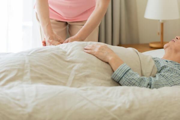 介護する職員とベッドに横たわる高齢者のイメージ写真