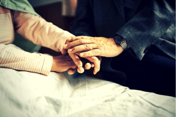 年老いた夫婦が手を重ねているイメージ写真