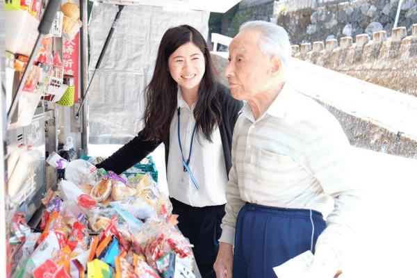 移動販売に同行するコミュニティナースと住民の高齢男性の写真