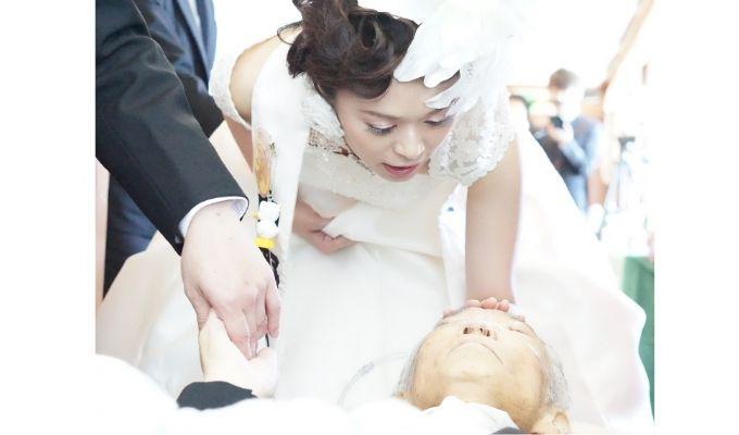 ストレッチャーで横になっている父の額にそっと手を触れる、ウェディングドレスの娘の写真