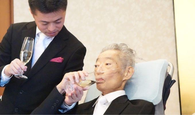 シャンパングラスを手にするがん患者の父親の写真