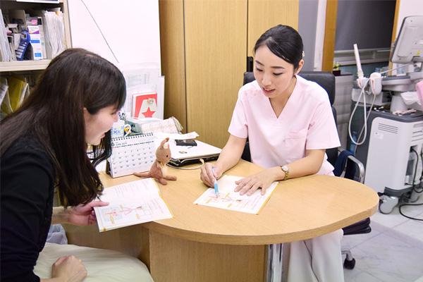 リーフレットを見せながら説明するれな先生と、話を聞く高柳さんの画像
