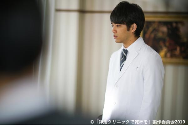 呆然と立ち尽くす演技中の主演で外科医約の三浦貴大さんの写真。