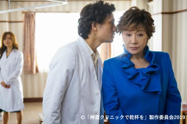 椿山大臣を演じる小林幸子さんに、耳打ちする外科医役の安藤政信さんの写真。