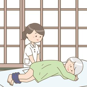 自宅で患者さんのおむつを交換する看護師のイラスト
