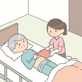 自宅で訪問看護師が患者さん(高齢男性)に温罨法(温湿布)をしているイラスト