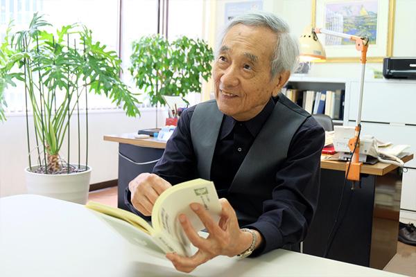 新刊の編集について説明する小南先生の写真