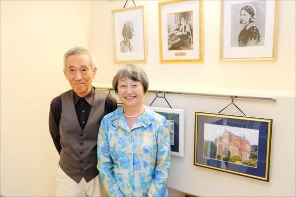 現代社の階段、ナイチンゲールの肖像やゆかりある写真の前に並ぶ小南吉彦さんと金井一薫さんの写真