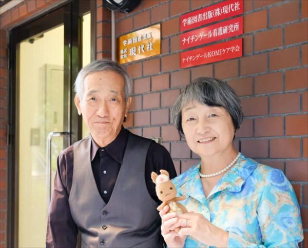 現代社の建物の前に並ぶ小南さんと金井さん、かんごるーちゃんの写真。