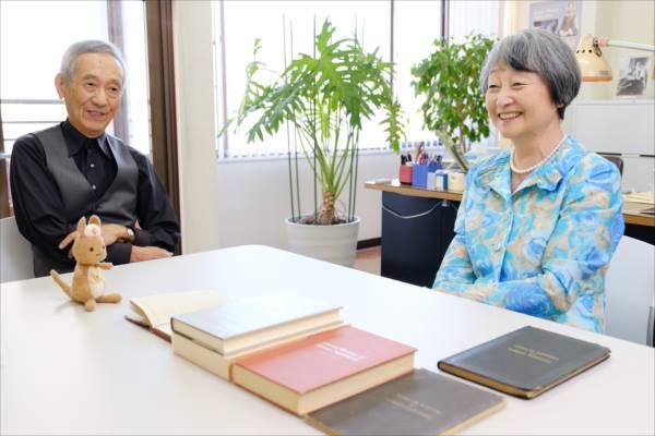 看護覚え書が並べられたテーブルに座って会話をする小南さんと金井さん、かんごるーちゃんの写真。