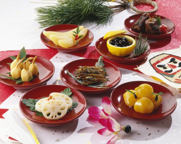 朱や赤の小鉢に盛り付けたおせち料理の写真