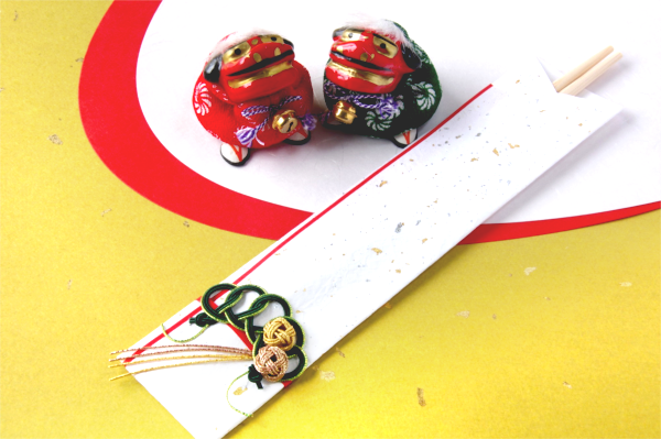 祝い箸と獅子舞の置物の写真