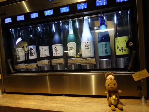 ワインや日本酒の瓶が並ぶ棚とかんごるーちゃんの写真。