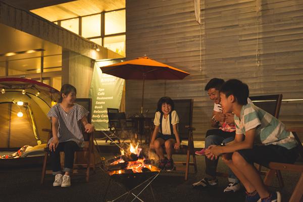 焚き火を囲んで楽しそうな4人家族の写真。