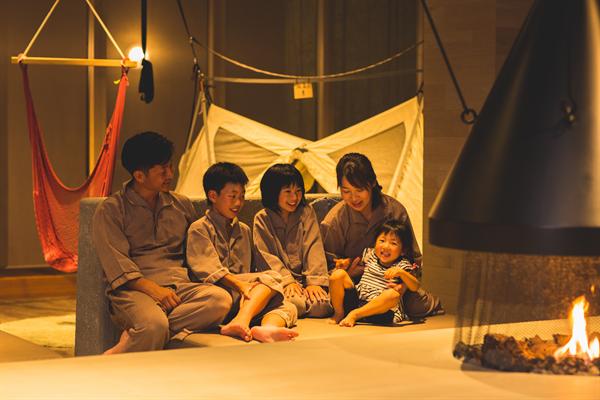 おしゃれな施設内でくつろぐ5人家族の写真。