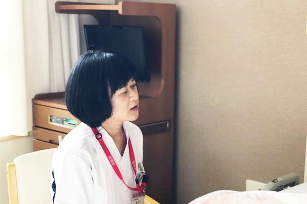 ベッドの患者さんに話しかける武見さんの写真