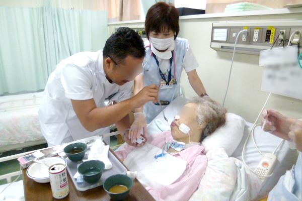 研修生の言語聴覚士へ、気管カニューレ留置中の摂食訓練を指導している場面